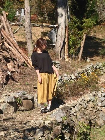 黒もからし色と相性のいい色です。からし色のギャザースカートを黒のスウェットトップスで引き締めながら、ローファー×靴下でガーリーな雰囲気をプラスした、秋らしいコーディネート。