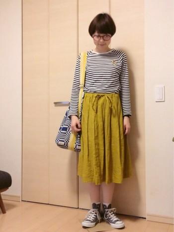 からし色のスカートが主役のコーディネート。ネイビーのボーダートップスとの相性抜群ですね!ヨハンナグリクセンのバッグ紐でからし色をリフレインさせているので、目線を上げる効果があります。足元はあえてカジュアルに仕上げて、絶妙なバランスに♪