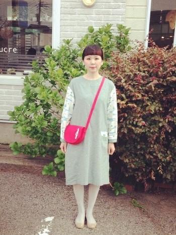 淡い緑がきれいなワンピースに、ハッとするような赤のポシェットをプラス。少女のような愛らしいコーディネートです。