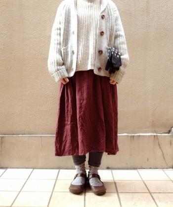 赤のギャザースカートにベージュを合わせると、柔らかく優しい印象に。