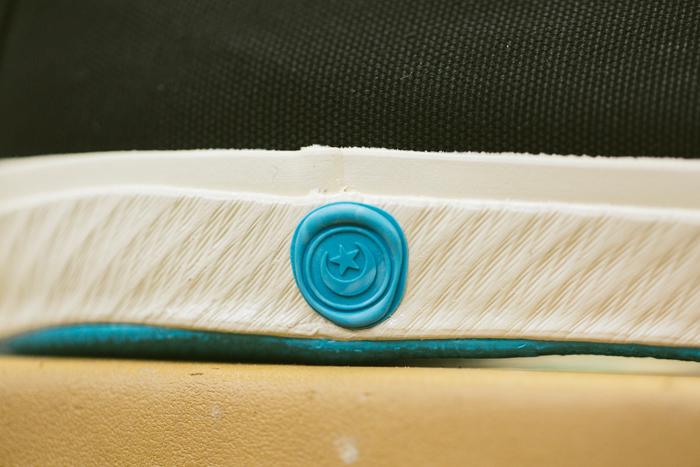 「シーリングワックス」に見立てたロゴマーク。布製のタグではなく「ゴム」のマークを付けているのも、ゴムにこだわりのあるムーンスターならでは