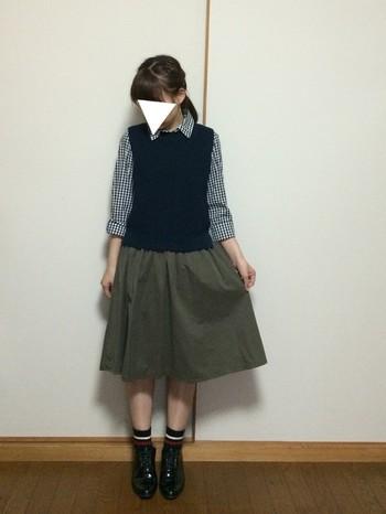 流行りのニットベストとギンガムシャツを合わせたスタイル。ネイビー×カーキ×ブラックのコーデで、より秋らしい印象に。