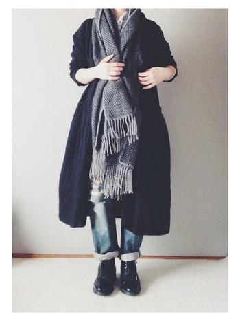 黒のワンピースを羽織ってまとめた、すっきりハンサムなモノトーンコーディネートに、ヘリンボーン柄のストールを無造作に首からかけて、さりげなくおしゃれ感をアップ。