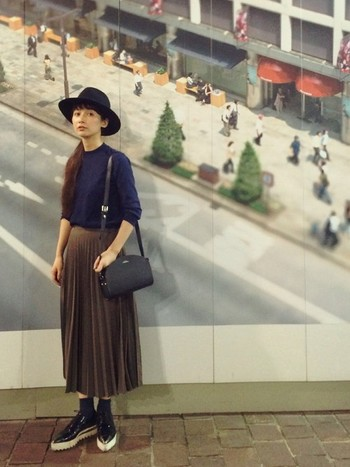 モデルのkazumiさん。女性らしいシルエットのプリーツスカートと小ぶりのバッグ、そこにメンズライクなハットと靴を合わせて甘辛のバランスをとっています。女性からも男性からも褒められるような素敵なコーディネートですね。