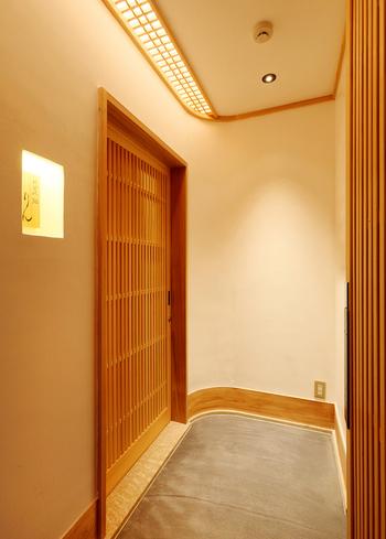 飯田橋駅から徒歩約4分。ビル2階にある玄関は白木戸で高級感があります。