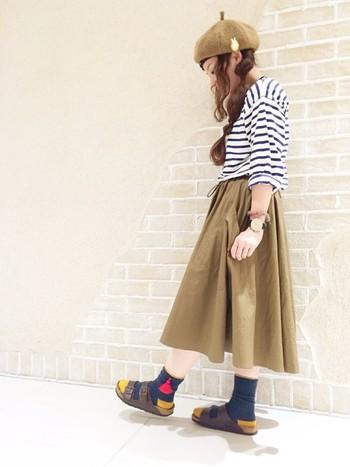 キャメルのベレー帽とスカートに、ボーターのトップスを合わせた爽やかなコーディネートです。ポイントのカラフルな靴下にあわせるビルケンはブラウンにして、ベレー帽やスカートと色味を統一するとバランスが良くなります。
