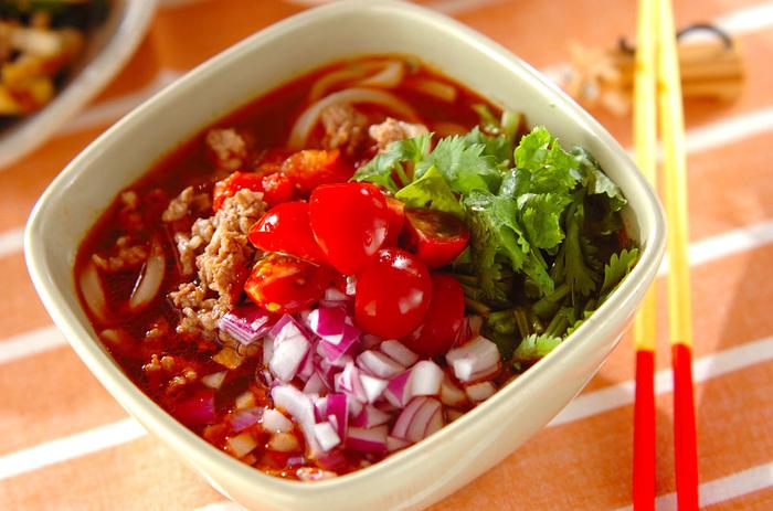 いつものうどんを、食欲の湧くアジアンな一品に!炒めた豚ひき肉に水煮トマトを加えたスープに、ナンプラーやラー油でエスニック感をプラスしています。上に香菜や紫タマネギ、プチトマトを飾れば色合いも綺麗ですね。