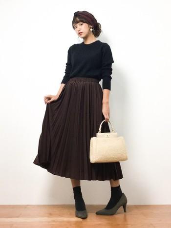 トレンドのロング丈プリーツスカートに、ヒールパンプスをあわせてフェミニンな印象に。ダークカラーでまとめたシックなコーデに、バッグが差し色になっています。