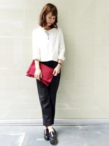白トップス&黒のストライプパンツ、黒のシューズとブレスレットでシンプルなコーディネート。差し色の赤のクラッチバッグは落ち着いた色合いなので大人っぽい。なにげなく、リップも赤で揃えている??