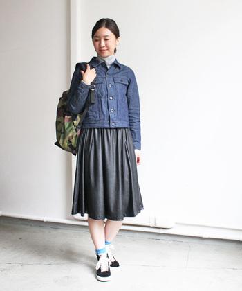 レザースカートというちょっとハードなアイテムも、デニムジャケットとリュックでカジュアルに。スニーカーの色もスカートと統一されていてオシャレですね。