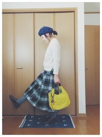 チェックのスカートとベレー帽で秋にぴったりのコーディネートに。濃い色のチェックでも、トップスが白のニットなら軽やかな印象になります。バッグは差し色で鮮やかな色にするとおしゃれです。