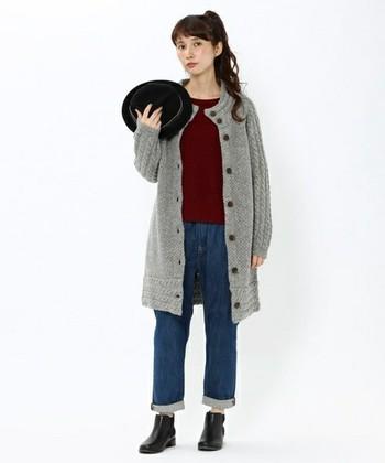 ケーブル編みがポイントになっているニットコートは、秋の流行カラーのグレーで。柔らかい印象なので、デニムとブーツでかっちりまとめるのもおすすめです。