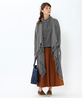 前が長めで後ろが短めになっている、フリンジが印象的なニットガウン。ロングスカートとも相性が良いですよ。