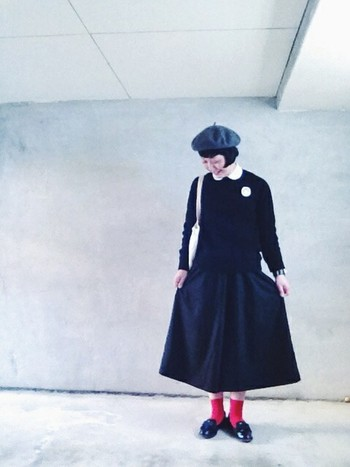 黒の中に、白いシャツの丸襟やブローチ、赤いソックスが映えるスタイル。グレーのベレー帽でさらにおしゃれに。