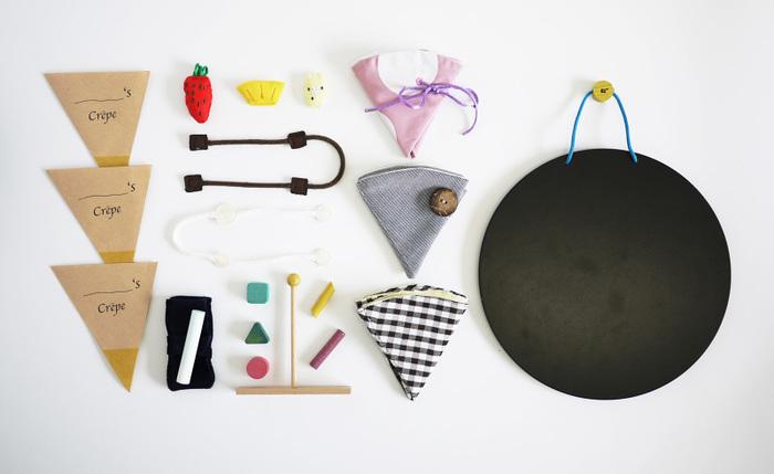 こちらはクレープ屋さんになりきることができるおもちゃ。クレープ生地、フルーツなどの具の他に、ホットプレート、トンボなどもついていて本格的。3種類の生地は布製で、巻きとめるところが、それぞれ紐、ボタン、ベロクロになっていて、子どもが自発的にボタン掛けやひも結びの練習ができるように工夫されています。