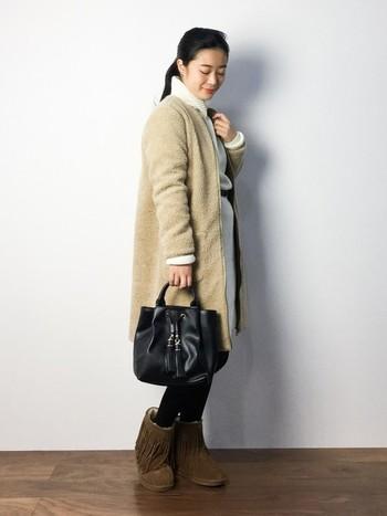 白のニットワンピに、ボアのコートを合わせたあったかコーデです。ニットワンピとボアコートが明るめの色なので、足元とバッグはダークカラーで引き締めましょう。