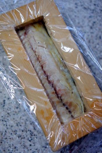 まず、押し型にラップをして、しめさばを全体に広げます。押し寿司の基本は上から下なので、一番上にくる鯖をはじめに入れます。