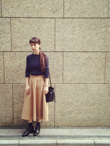 ミモレ丈のふんわりしたスカートは、寒い季節にぴったりな暖色カラーを選ぶと落ち着いた印象になってgood! ちょっと難しそうな、紫色のニットもインして分量を少なくすれば、すっきりまとまったコーデになっています。