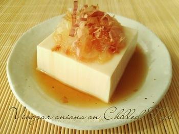 豆腐に、酢たまねぎ鰹節をのせ、めんつゆをかけただけの簡単レシピです。おろし生姜をのせたり、ミョウガやアサツキなどをのせても良いですね。 お酒のおつまみになりそうです。