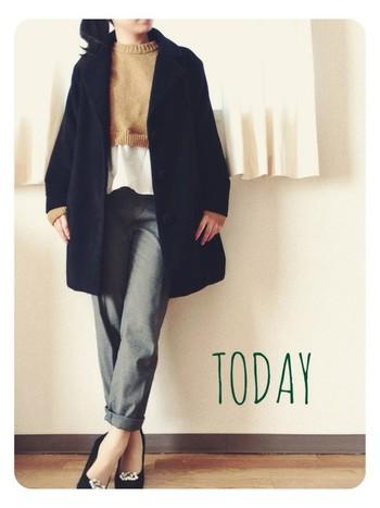 グレーのタックパンツと黒のコートを合わせるとシンプルになりますが、裾がフレアになったニットがポイントになっています。秋色のニットを選ぶと旬のコーデになりますよ。