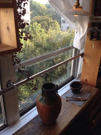 明るい窓辺にはガラス瓶や棚がディスプレイ。光が調和する空間。