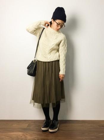 白ニットとカーキのチュールスカート以外を黒で統一しているコーデ。ニット帽でこなれ感が出ています。ニット帽と詰まり気味な襟元の相性も良いですね。