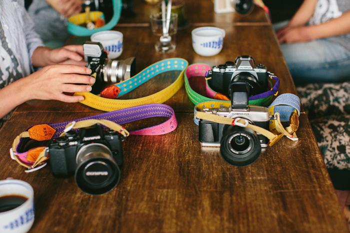 7人が色違いで持っているカメラストラップは高松市を拠点に活動しているFURIKAKEさんのもの。小豆島カメラのロゴ、オリジナルのTシャツはMOTOKOさんの知人であるイラストレーターCHO-CHAN(チョーチャン)さんがデザイン