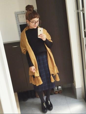 濃紺チェックのスカートとリッチな質感のキャメル色大判ストールがお似合いのコーディネートは、お団子ヘアとダテメガネでフレッシュ感のある装いに。