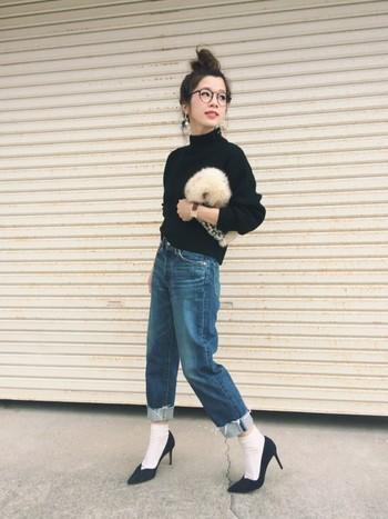 シンプルな黒のトップスにジーンズを合わせたスタイル。切りっぱなしの