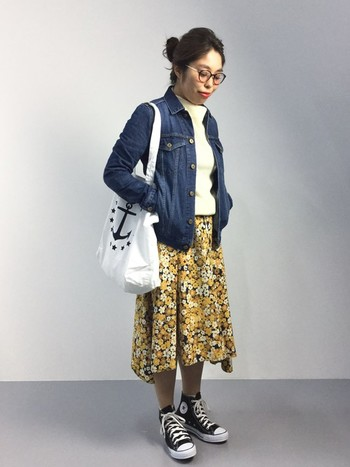 デニムジャケットに個性的なフラワープリントのスカート、そして白ニットというレトロ感のあるスタイルを黒のハイカットのコンバースが、すっきりまとめてくれているようです。