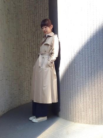 ロングトレンチのベルトを結んで、トレンチコートらしい上品なシルエットです。 コートの裾から覗く、パンツと白のコンバースが、今年らしいスタイルを作りあげてくれています。
