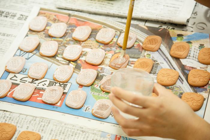 成型したブローチに釉薬を塗っているところ。ムラが出ないように、表面に刷毛で釉薬をしっかり塗ってから、再び全体に釉薬をつける作業をするのだそう