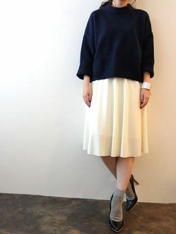 空気感のある白のスカートに、薄手のグレーの靴下を合わせて上品なコーデに仕上がっています。色を絞ったシンプルコーデに手元のバングルでアクセントを。
