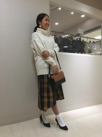 白のニットと、チェックのスカートが冬らしいコーデです。ミモレ丈のスカートには、タイツを合わせるのではなく、あえて靴下を選べばトレンドを抑えたこなれた印象に仕上がります。