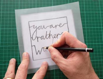 下絵の上にトレーシングペーパーをのせて下絵を鉛筆でなぞります。はじめのうちはあまり細い文字にすると切り抜きにくいので注意しましょう。
