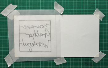 下絵をトレースしたら、台紙の紙をカッターマットの上にマスキングテープで固定し、さらにトレースしたトレーシングペーパーも片側に固定します。