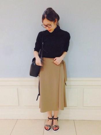 おすすめのボトムのカラーのひとつ、キャメル。ベージュよりも濃い色なので、肌に浮かずコーディネートに取り入れやすい色。巻きスカートだと、大人っぽく女性らしい雰囲気が演出できるので、ブラックのトップスと組み合わせて、こんなレディスタイルはいかがでしょう。