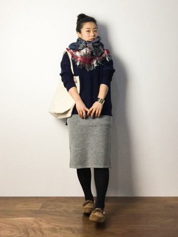 シンプルなスカートと黒タイツに合わせると、モカシンの色が映えますね。首元も大判のストールを巻いて、寒さ対策もばっちりなコーデの完成です。