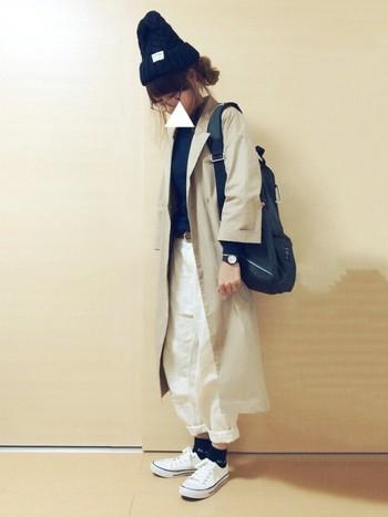 ネイビーのニットや白のパンツと靴。全体を同じ色に揃えて、ロングトレンチですっきりと。