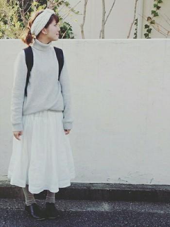 ライトグレーのニット、白のスカートにアイボリーのヘアバンドがマッチしています。トーンを合わせることでとても落ち着いた統一感のあるコーデになりますね。