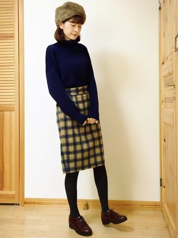 チェックのタイトスカートが大人の女性らしさを感じるシルエット。帽子と色を合わせて落ち着いた色合いでまとめているのもポイントですね。
