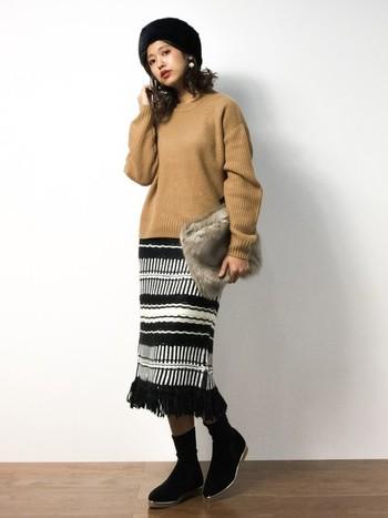 個性的なパターンのスカートが印象的なスタイル。黒のファー帽子がシンプルながらも大人の雰囲気を加えてくれます。黒い帽子はパールのピアスが映えますね。