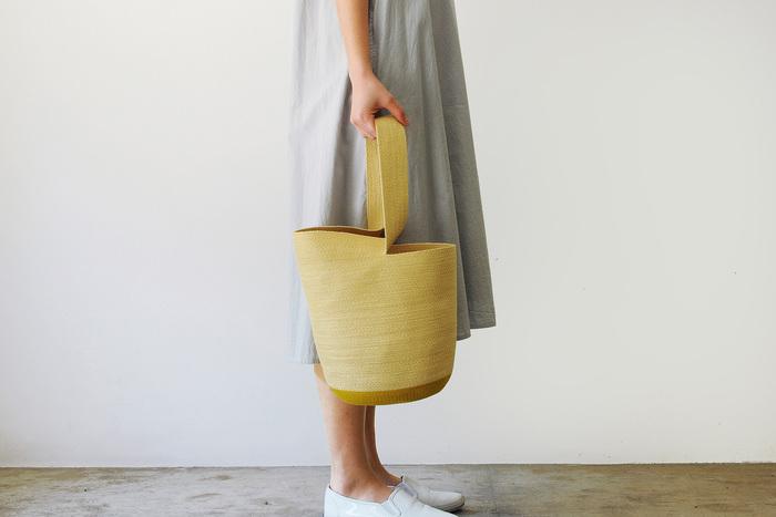 帽子のような編み方が独特な糸のラウンドバッグ。肩にかけると口が閉まります。