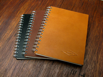 消耗品であるノートに革を使用した珍しい「レザーリングノート」。革の個性を見極めながら1枚1枚ハンドカットされた表紙は、使い込む程に柔らかさや味わいが増し、自分だけのノートに変化していきます。ワンポイントになっているロゴの型押しも、ひとつひとつ丁寧にハンドプレスされています。
