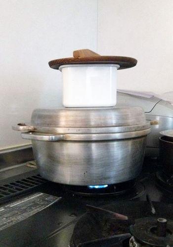 蓋が平らで丈夫な作りの「無水鍋(R)」。その形状と保温性の高さを生かして、こんなアイデアも!調理中の「無水鍋(R)」の上に別の鍋を載せて、もう一品の下ごしらえ。直火ではないので、ぐつぐつ沸騰するまではいかないけれど、ちょっと何かを温めたい時にぴったりです。エネルギーもスペースも節約できてしまいます。