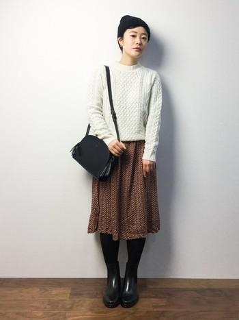 ガーリーな花柄ワンピと、手編み風ニットの組み合わせがかわいらしいスカート風のコーデです。バッグやブーツを黒で統一すると、甘くなりすぎずバランス良い感じに。