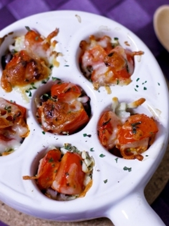 耐熱皿に、一口大に切ったたこ、みじん切りニンニクとスイートバジル、塩こしょうを入れ、その上にプチトマト、とろけるチーズ、オリーブオイルを載せてオーブンで焼きます。写真のような耐熱皿がない場合は、小さめのココットを使うとおしゃれにできそうですね。