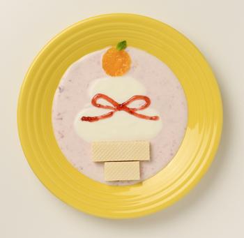 いちごジャムを混ぜ、ピンクの背景を作った立体感のあるシーズンアート。今年はこんなキュートな鏡餅でお正月を過ごしてみては?   【材料】 ・明治ブルガリアヨーグルトLB81プレーン 120g ・いちごジャム 適量 ・みかん(缶詰) 1個 ・ミントの葉 1枚 ・ウエハース(薄茶色・2cm×10cm) 1枚  【作り方】 ①缶詰のみかんを半分に切り、開いてみかんの実の形にします。 ②ウエハースを2:3の比率(4cmと6cm)にカットします。 ③ジップ付きの袋にいちごジャムの半分を入れ、袋の端を斜めに5mmカットします。 ④プレーンヨーグルトから大さじ2を取り分け、残りのプレーンヨーグルトにいちごジャムの適量を混ぜてボウルに入れます。 ⑤④で取り分けたヨーグルトで、かがみ餅の形を作ります。 ⑥⑤の上に①のみかんを乗せ、ミントの葉を飾ります。 ⑦ウエハースの長い方を餅の下に置き、その下に短い方を置いて台にします。 ⑧いちごジャムで、水引き(リボンの形)を描きます。