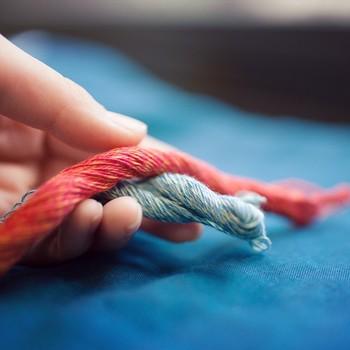 極細のコットンの糸を何本も何本も束ね、数十本を1本の太い糸にする「杢糸(モクイト)」を織り込んだスカーフ。