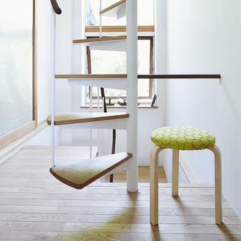 階段の踊り場や廊下などの小さなスペースにもさりげなく置けるスツール60。鮮やかでやさしいイエローのタンバリン柄が、空間に心地よいアクセントを生みます。